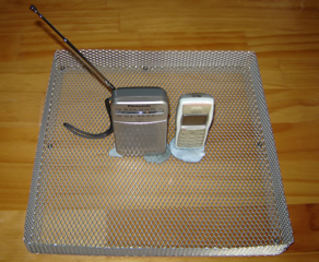 Cell phone and AM/FM radio in the open cage